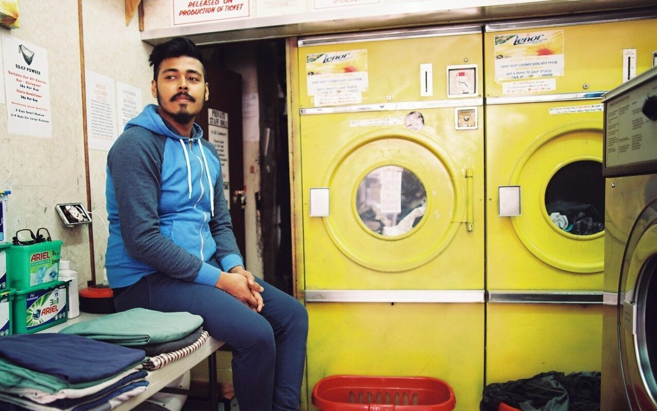 Young man working in a launderette