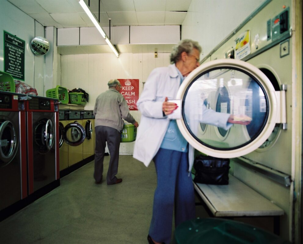 Woman loading up dryer in a launderette