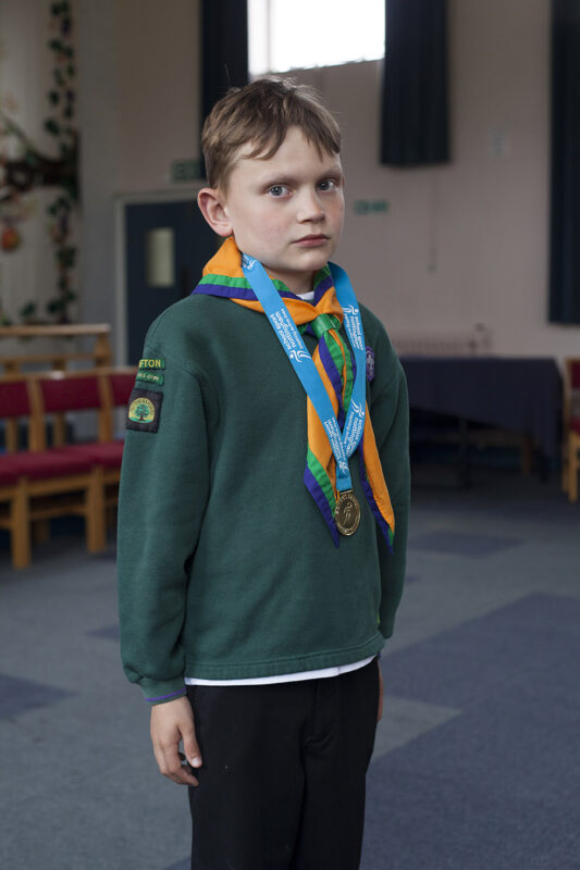 Boy in scout uniform looking proud