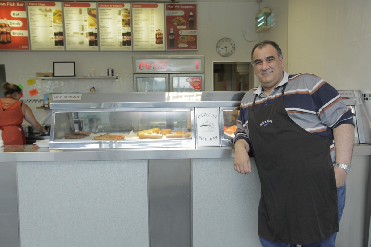 Man in a chip shop wearing an apron and leaning on the counter