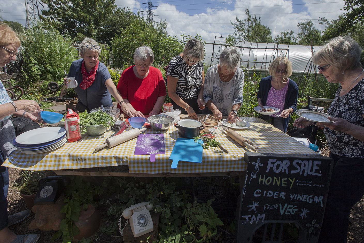 People collectively making food at a large table in an allotment garden