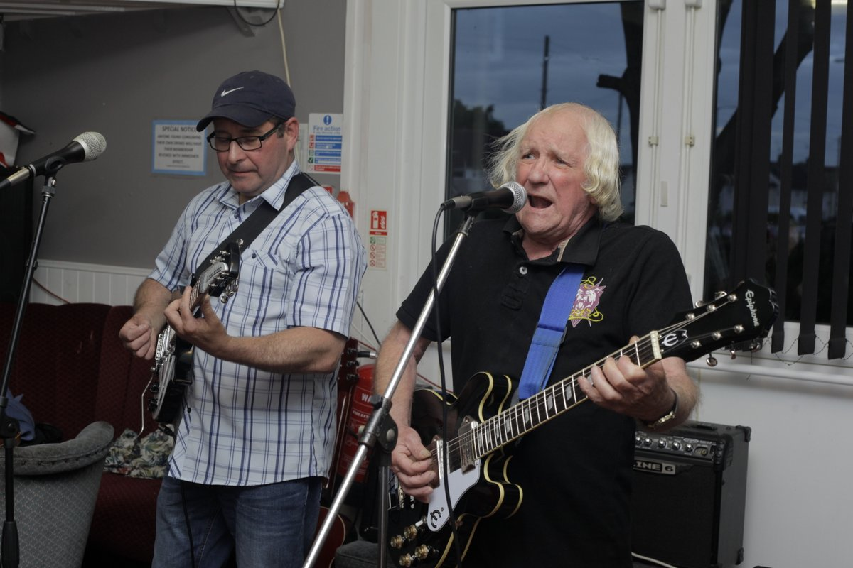 Two men playing electric guitar in a community centre