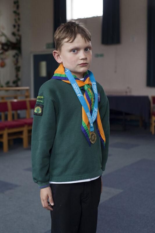 Boy in scout uniform looking proud
