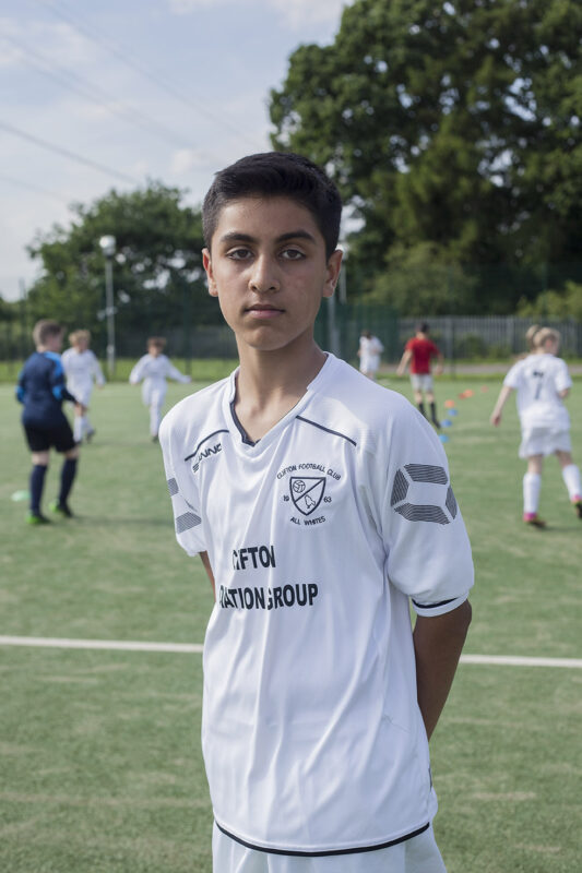 Young boy in white football kit