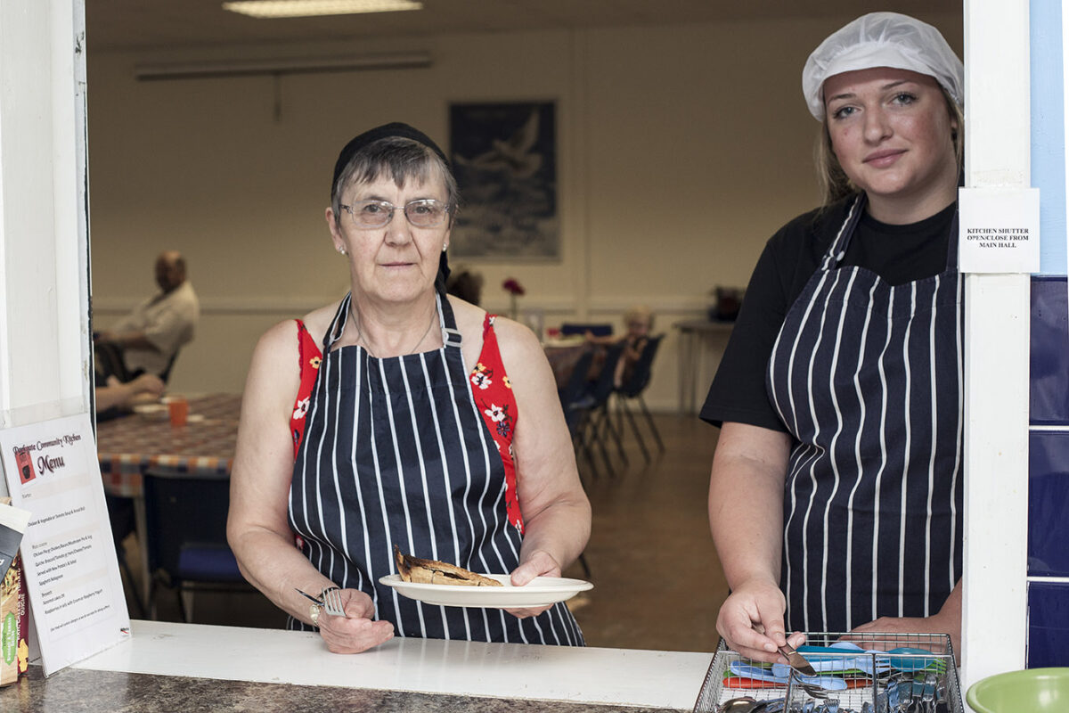 Two women wearing aprons and serving food through a serving hatch