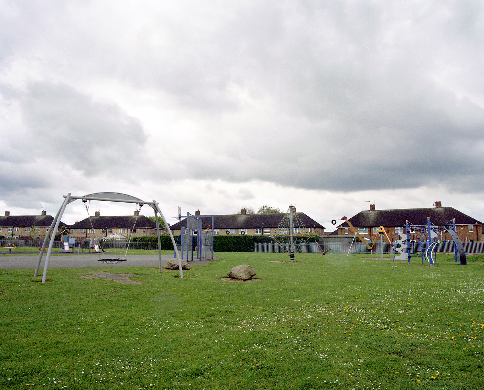Image of a children's playground with semi detached housing in the background
